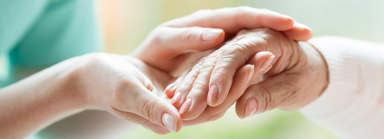 pair of hands holding elderly hand