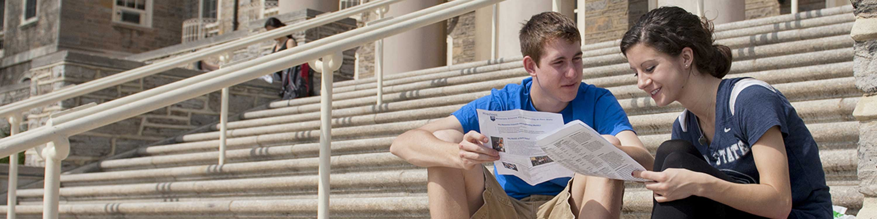 students on sitting on steps of old main